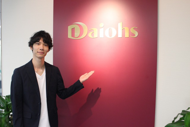 Daiohsの社名プレートに手をかざしている男性の写真