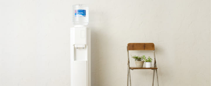 観葉植物が飾ってある椅子の横に設置されている信濃湧水のウォーターサーバー
